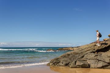 Man on the rocks looking at the ocean,  near El Cotillo, Fuertev