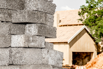 Stacked concrete bricks infront of house bein build