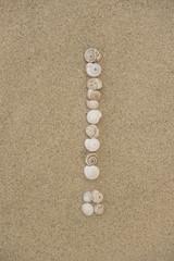 Ausrufezeichen aus Schneckenhäuschen im Sand