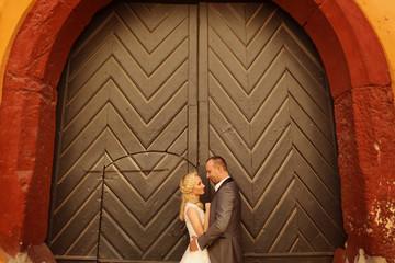 Bride and groom against big green door