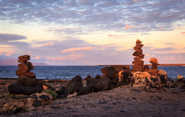 Cairns of balanced stones  bulit by the Ocean at Faro de El Tost