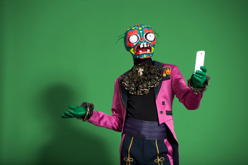 Actor in pink suit and mask zombie holding phone.