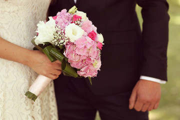 Detail of bride and groom hands with wedding bouquet