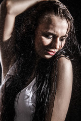 Sexy young woman dancing under the rain
