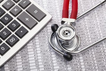 Health. Stethoscope and calculator on document with digits