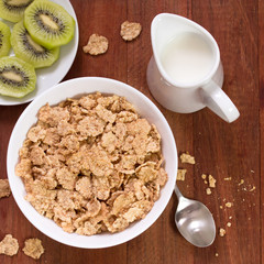 cereals in white bowl, milk and kiwi