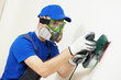 plasterer worker with sander at wall filling
