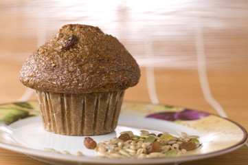 Bran and Raisin Muffin with Mixed Nuts on a Plate