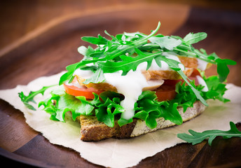 Rye toast with green leaf, tomato and chicken