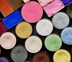 photo of colorful set of eyeshadows textured background