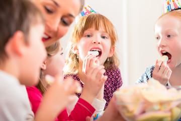 Kinder auf Party naschen Süßigkeiten