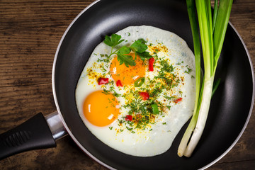 two frying eggs in pan on table
