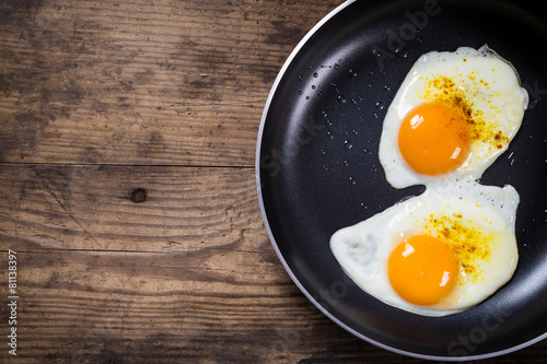 two frying eggs in pan on table - 81138397