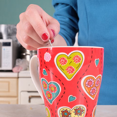 Close up of woman's hand stirs the tea in a cup