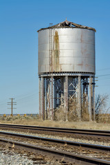 Old rustic water tower along a railroad