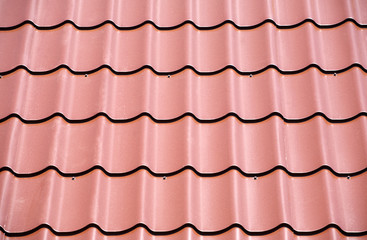 Fragment of red metal roof with many as background closeup