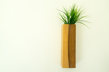 Wooden flowerpot hung on the white wall