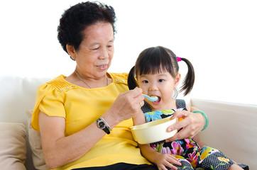 Asian senior woman feeding her grandchild