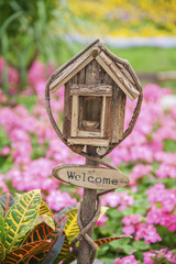 Ornate Mailbox with welcome sign in colorful garden