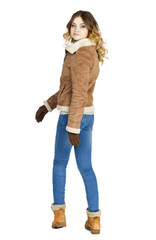 Young beautiful girl in a leather sheepskin coat and blue jeans