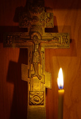 Burning candle and ancient Christian cross. Focus on a cross
