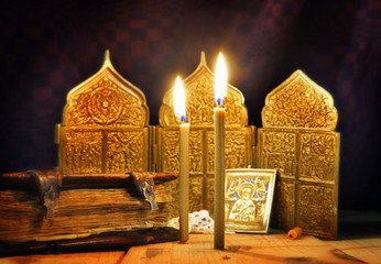 Ancient icons and burning candles. Focus on candles