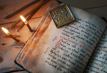 Christian still life with burning candles and old Psalter