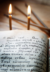 Christian still life with burning candles and open ancient book