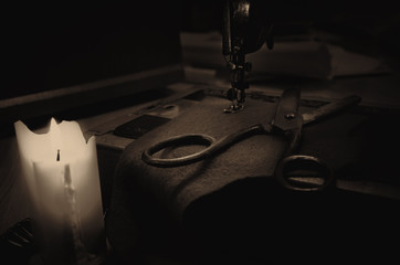old sewing machine, fabric and rusty scissors at the light candl