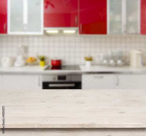 Tuinposter Koken Wooden table on red modern kitchen bench interior background