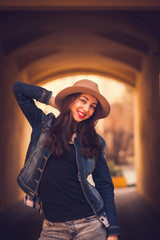 cheerful girl in hat posing on the street and smiling