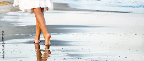 Leinwanddruck Bild Woman walking on sand beach