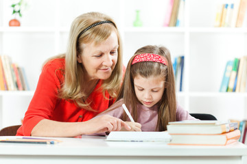 Grandmother helping little girl to learn to write