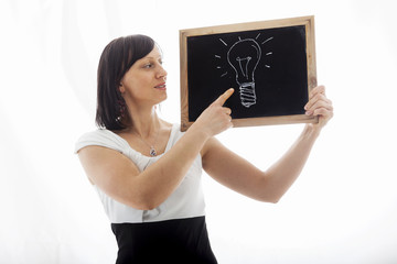 businesswoman shows doodle of a lightbulb on blackboard