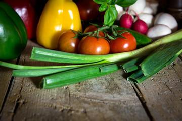 Viel frisches Gemüse und Kräuter auf altem Holztisch