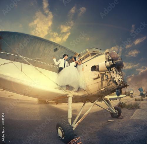 wedding couple on vintage plane wing at sunset - 81153926