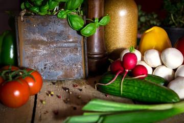 Holztisch mit viel frischem Gemüse und Kräuter, altes Schild m