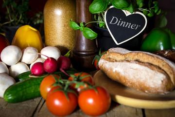 Holztisch mit viel frischem Gemüse und Kräuter, Herz mit Wort