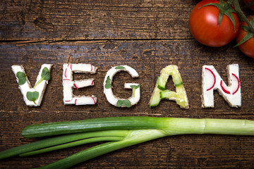 Wort Vegan aus verschieden belegten Broten auf Holztisch