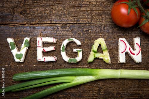 Fotobehang Groenten Wort Vegan aus verschieden belegten Broten auf Holztisch
