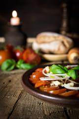 Tomatensalat mit Zwiebeln und Basilikum auf altem Holztisch mit
