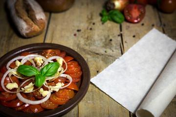 Tomatensalat mit Zwiebeln und Basilikum auf altem Holztisch, Sch