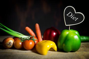 Auswahl verschiedener Gemüse auf altem Holztisch, Herz mit Wort