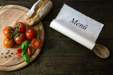 Tomaten und Brot auf Holztisch, Schriftrolle mit Text Menü
