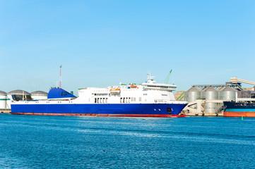 Modern blue cargo ship in Lithuanian harbor of Palanga.