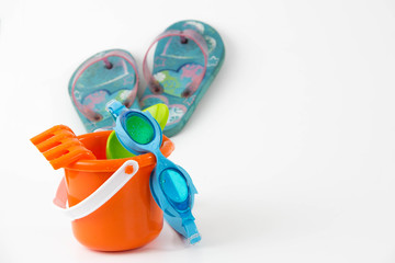 summer toys bucket with spade goggles flip flops isolated on whi