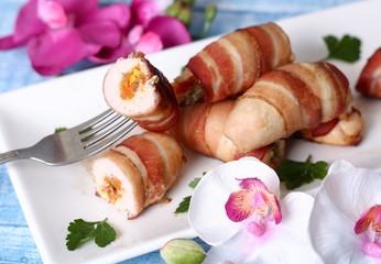 Chicken rolls stuffed with vegetables wrapped in bacon