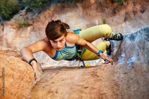 Leinwanddruck Bild Rock climber climbing up a cliff