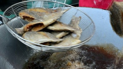 Deep fried Gourami in a hot boiling pan in Thai cooking style