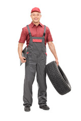Mechanic holding a tire and clipboard